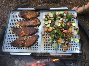 Photo of steak and veggies grilling over a campfire