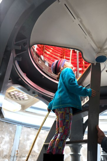 A photo of a girl climbing into the light to view the prisms of the Umpqua Lighthouse