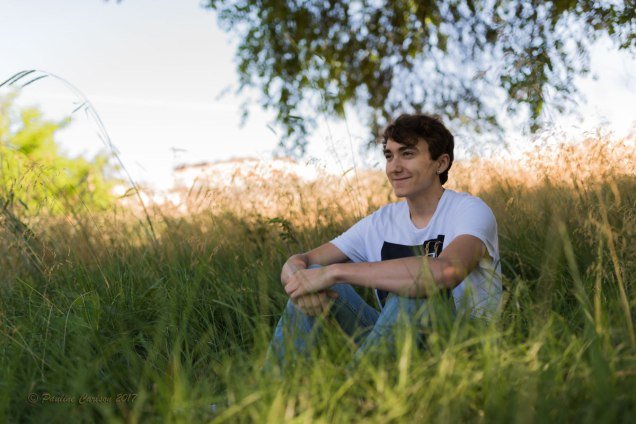 Photo of teen boy in tall morning grass