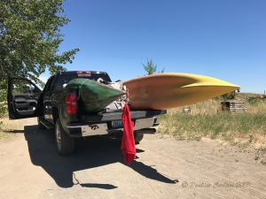 Photo of truck loaded with kayaks and red warning flag