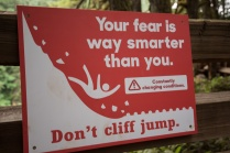 Photo of a red warning sign to prevent cliff jumping