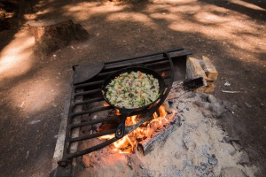Photo of breakfast being cooked in a cast iron skillet over a fire.
