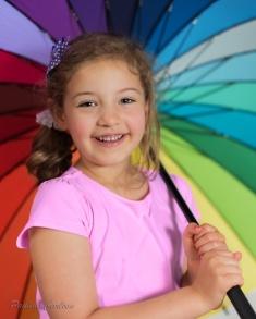 Photo of girl with a rainbow umbrella