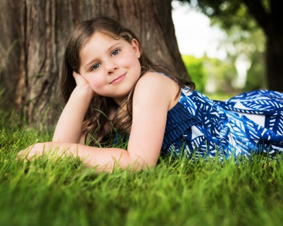 Photo of girl lying down in front of tree.