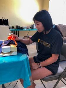 Misty-Jade sewing tassels onto her blanket.