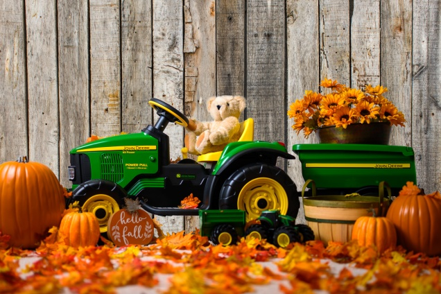 Pauline's Photography with child's John Deere tractor in front of old barn wood wall.